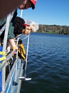 An image of CSLAP volunteers on the back of a boat observing how to properly collect secchi disk measurements.