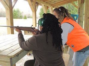 woman learning how to shoot a rifle with the help of an instructor