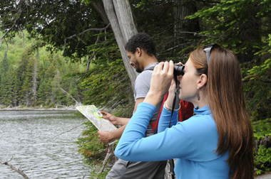 woman and man using binoculars to look for birds