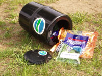 Image of a bear resistant canister with food packets inside.