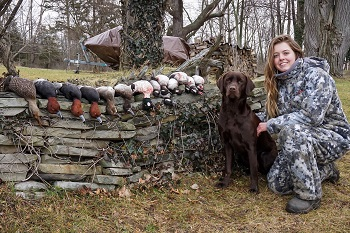 Female duck hunter with harvested ducks and retriever