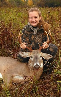 Young female hunter with harvested mature buck
