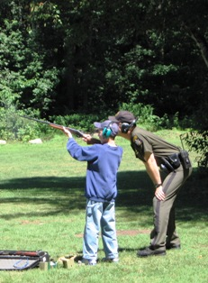 instructor teaching a boy how to use a firearm