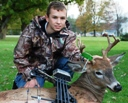 Young male bow hunter poses with the buck he killed