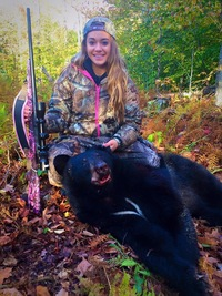 An teenage girl with a bear she shot