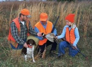 Pheasant hunters with their dog and their taken duck