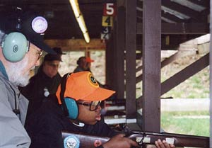 An instructor teaches a future hunter to handle a firearm safely.