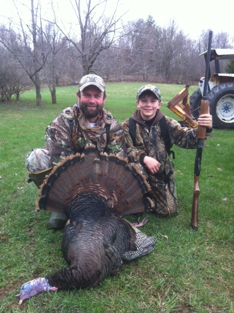 A youth hunter with his father and their turkey