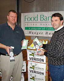 Two men holding some donated venison in packages at a food bank