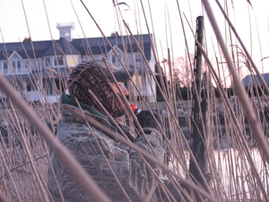 A waterfowl hunter in front of a residence.