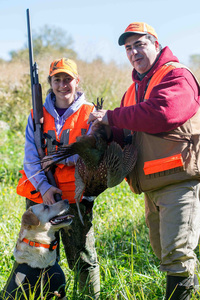 A successful youth hunter with her father and hunting dog.